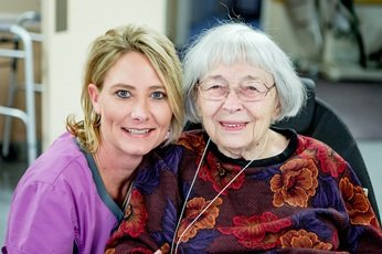 Smiling resident and caring nurse