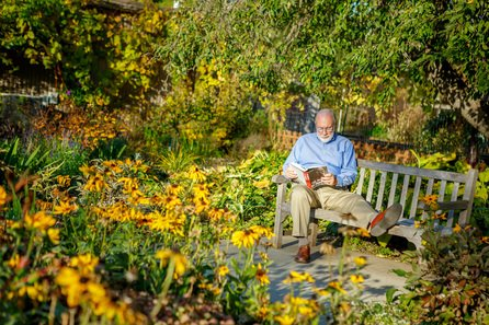 retired man reading in a garden